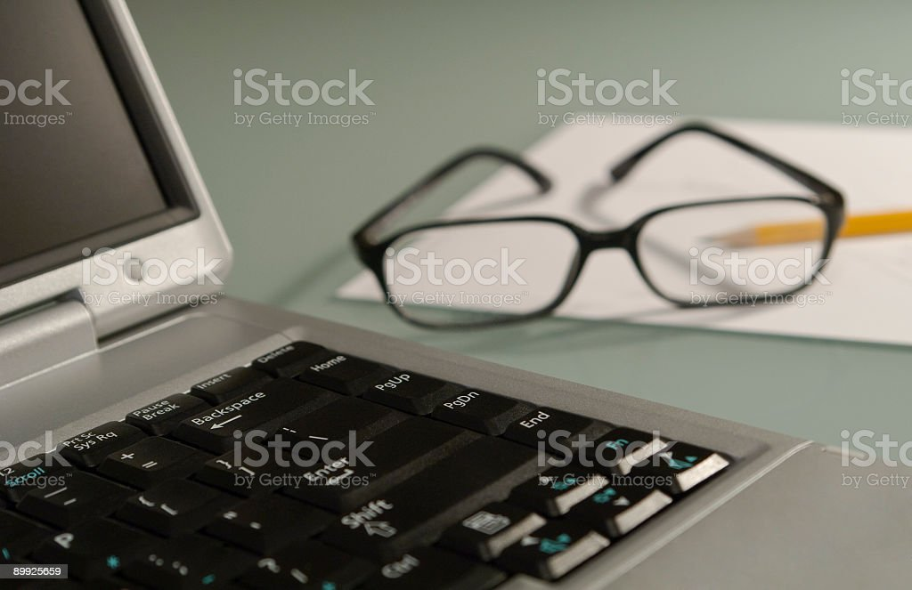 A laptop with paper and eye glasses stock photo