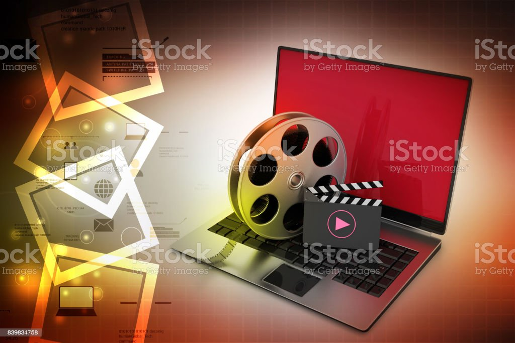 Laptop with reel wheel and clap board in color background stock photo