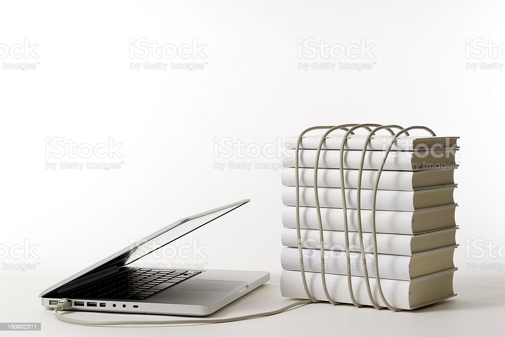 Laptop with stacked blank books and cable on white background royalty-free stock photo