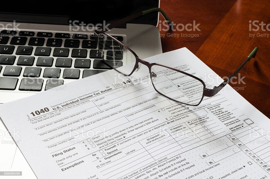 1040 income tax return form with MacBook and glasses stock photo