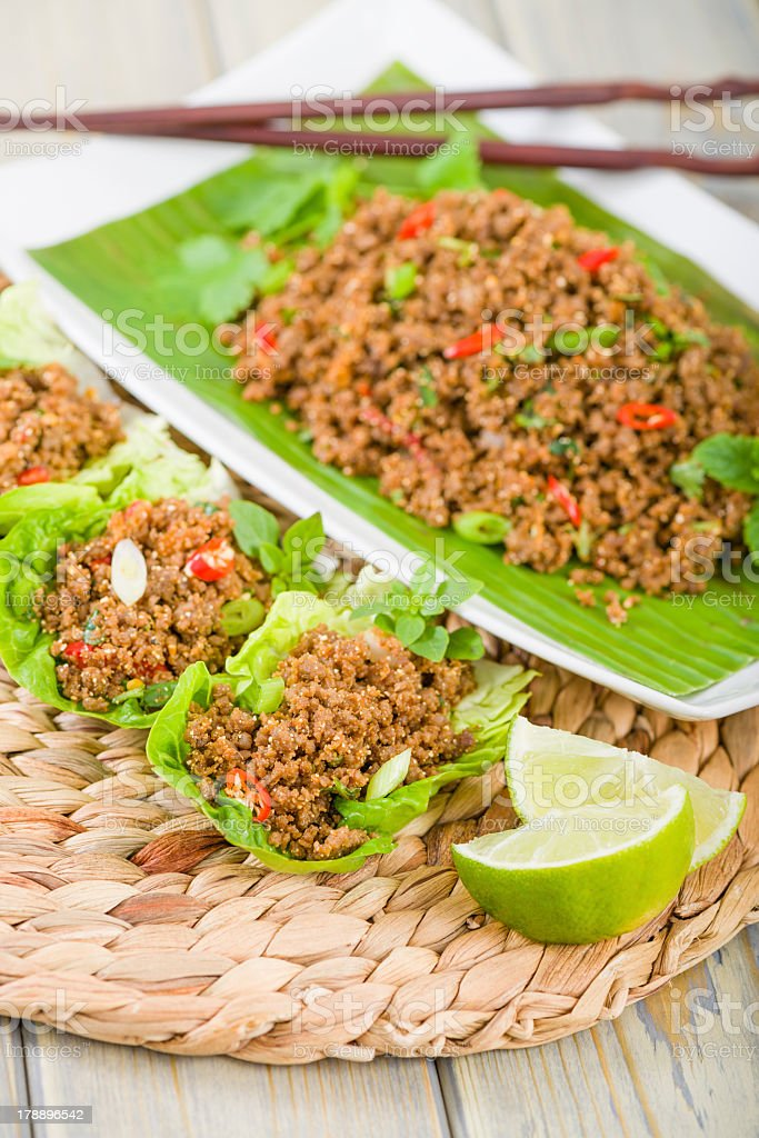 Larb on a green plate and served in lettuce leaves stock photo
