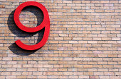 Large 3D red nine symbol in sunlight on brick wall