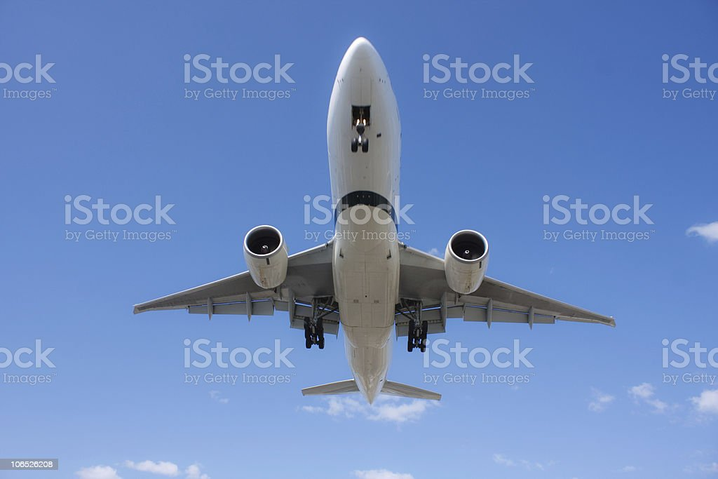Large airplane flying directly above the camera stock photo