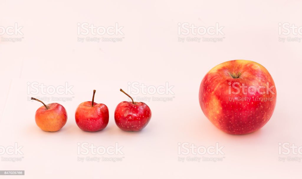 A large apple and behind it are 3 small paradise apples. The boss is ahead of him subordinates. Team of business employees. stock photo