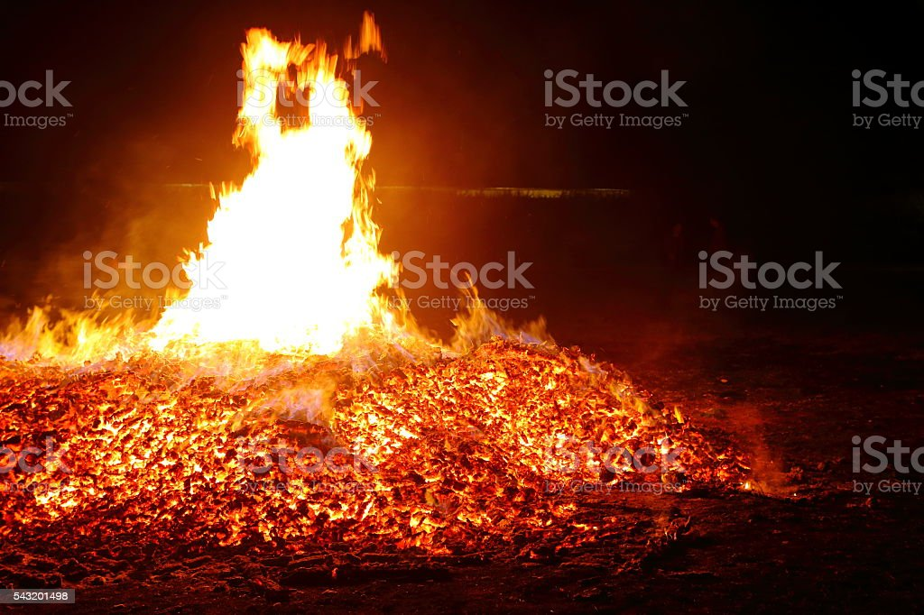 Large ash heap and burning embers flaming bonfire in summer stock photo