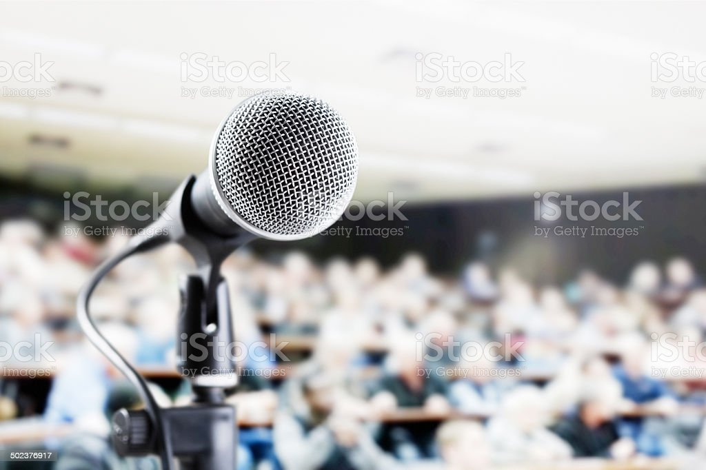 Large audience in auditorium with vocal mic await speaker stock photo
