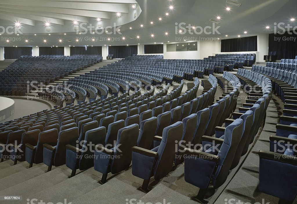 A large auditorium with several rows of blue chairs stock photo