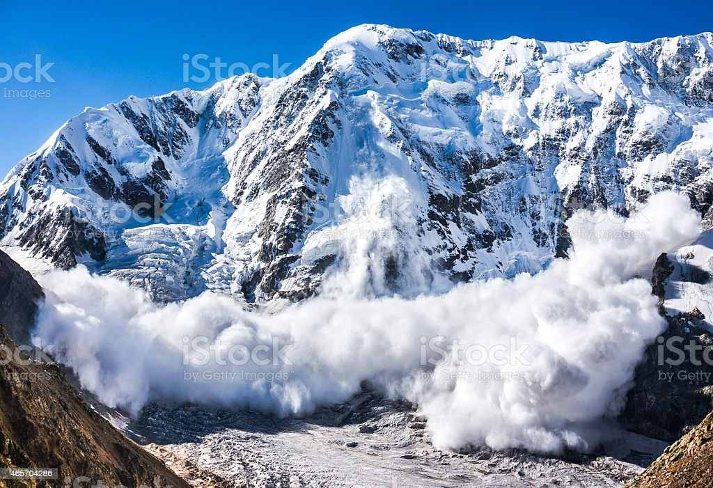 Large avalanche coming down the rocky Caucasus mountain stock photo