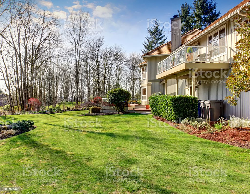 Large luxurious back yard with greenery, and furnished back porch.