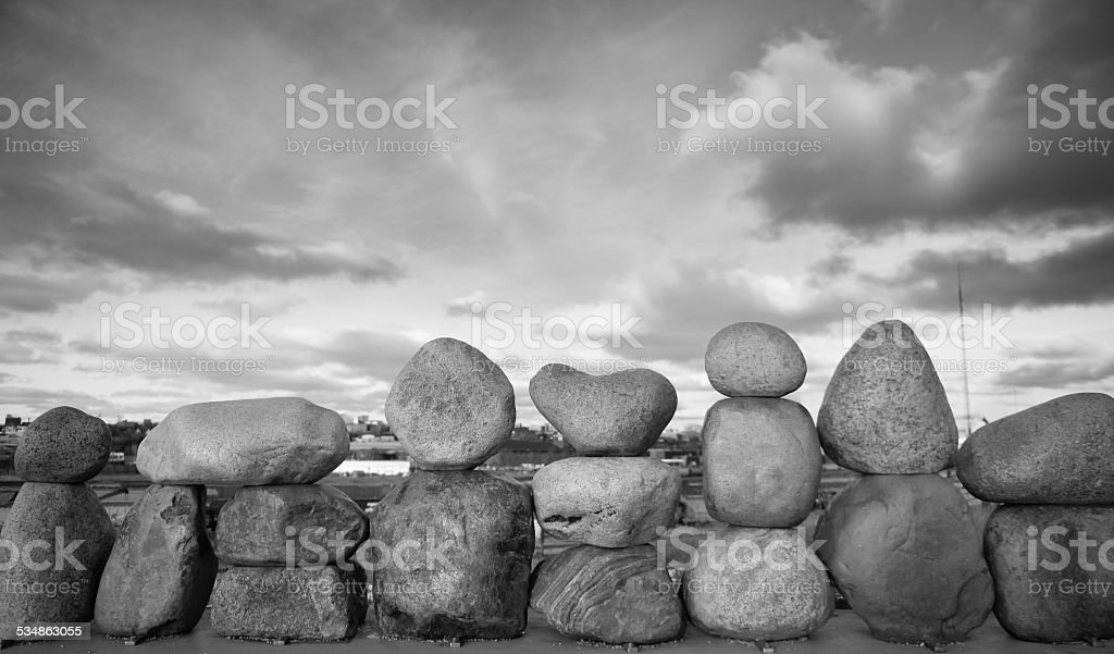 Zen-like large rocks balancing on top of each other in black and...