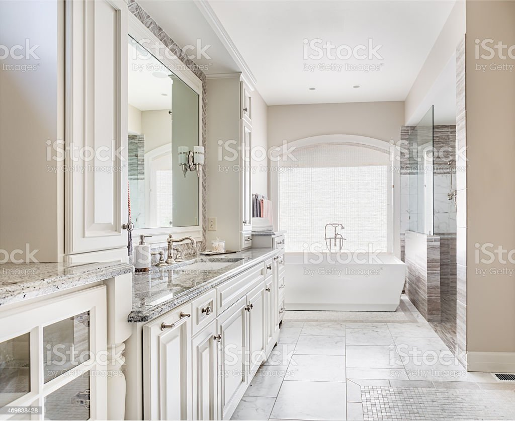 Large bathroom in luxury home with sink, bathtub, and cabinets stock photo