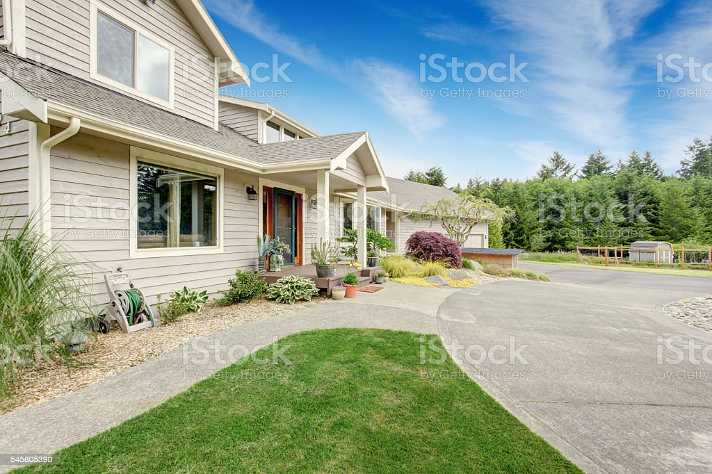 Large beige house with white trim, and well kept lawn stock photo