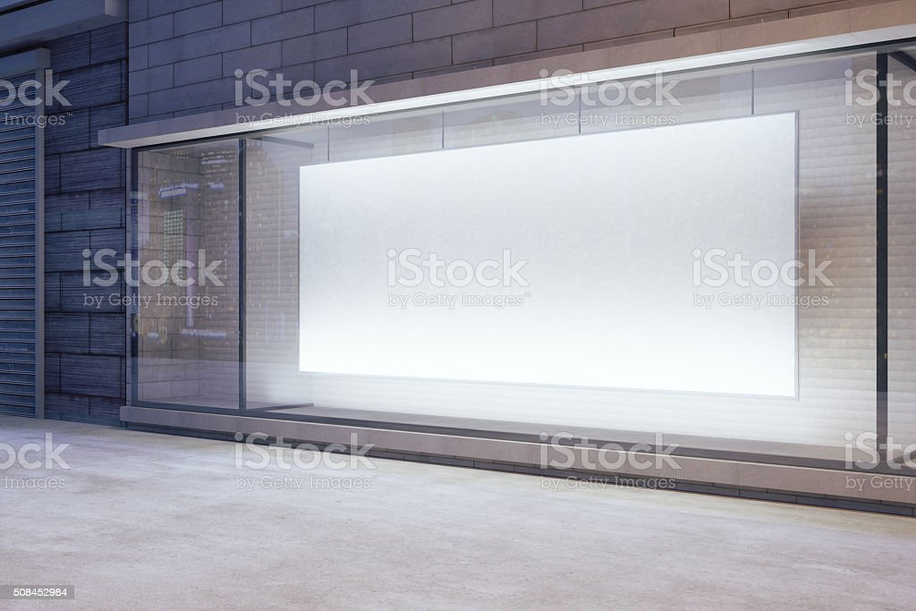 Large blank banner in a shop window at night stock photo