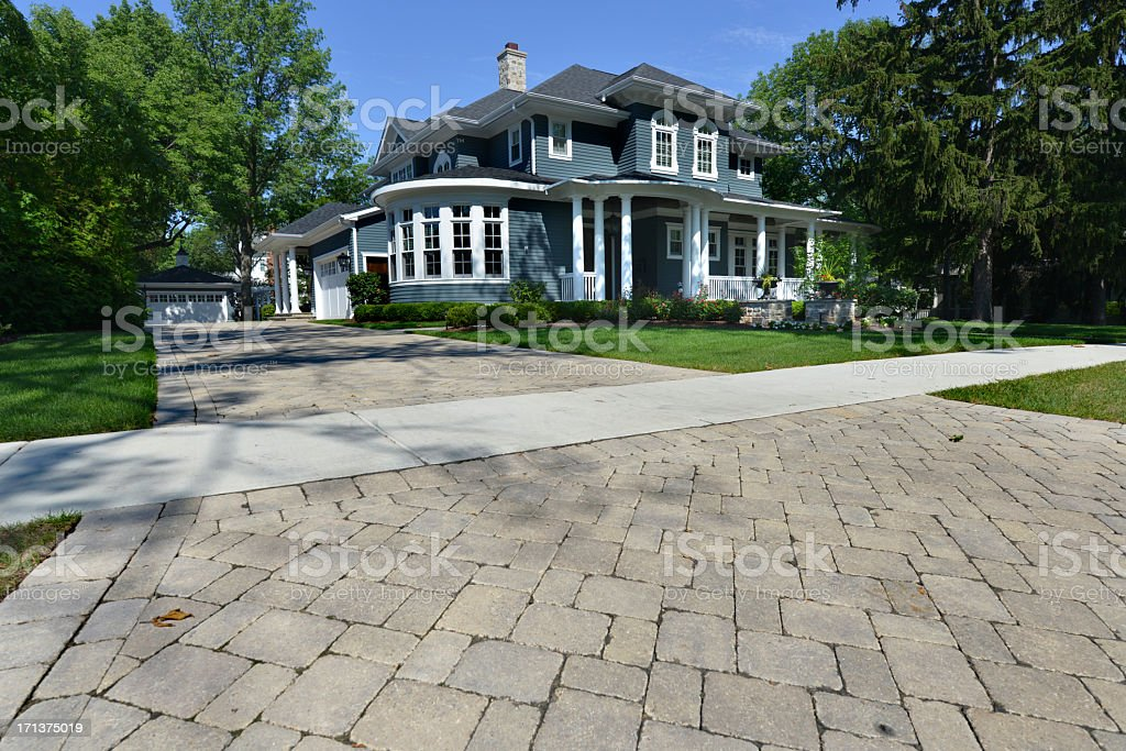 Large blue house on a lot with a long driveway stock photo