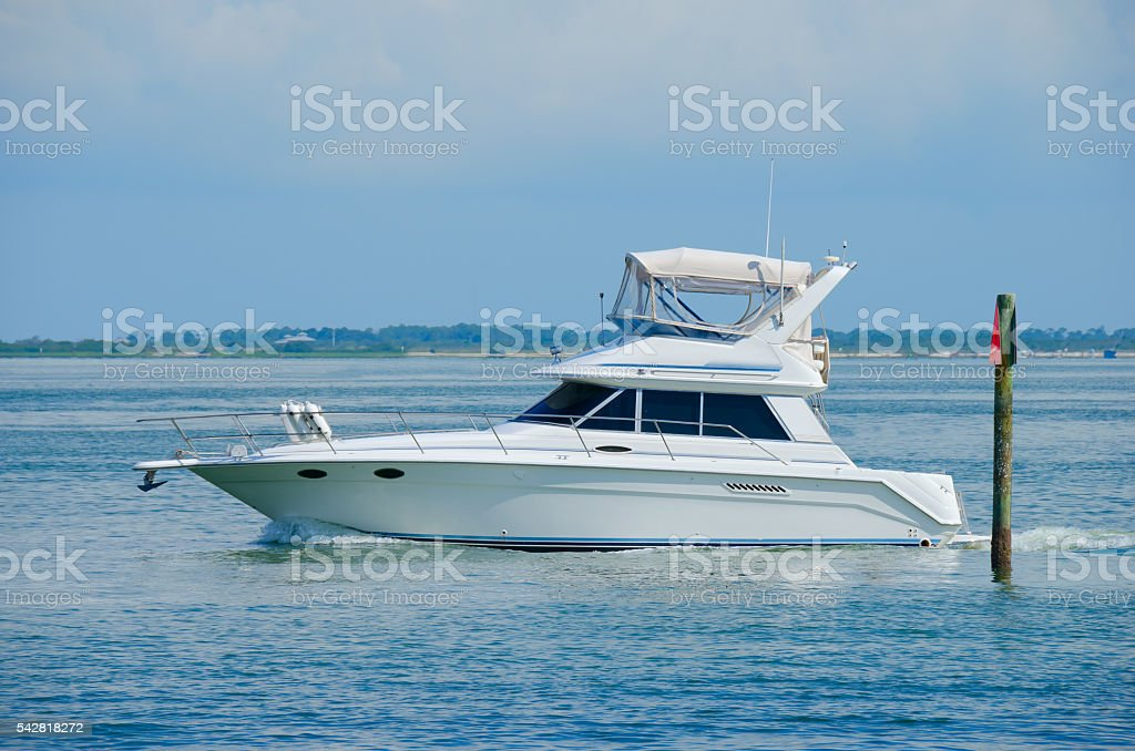Large boat yacht cruising by channel marker stock photo