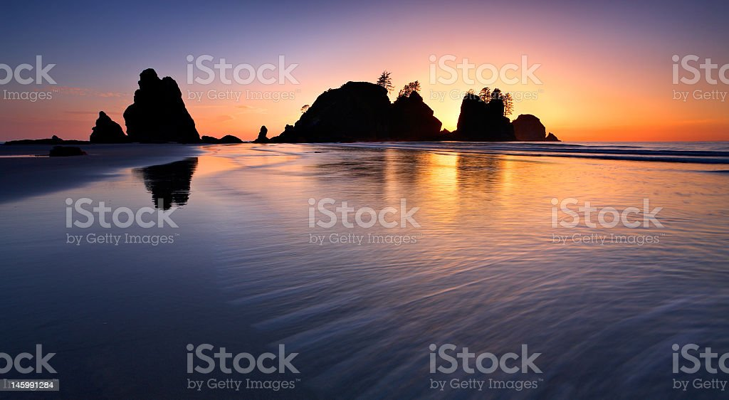Large body of water in the sunset Silhouetted rocks central stock photo