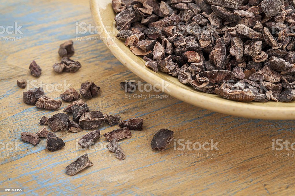 Large bowl of raw cacao nibs spilling on wooden table stock photo