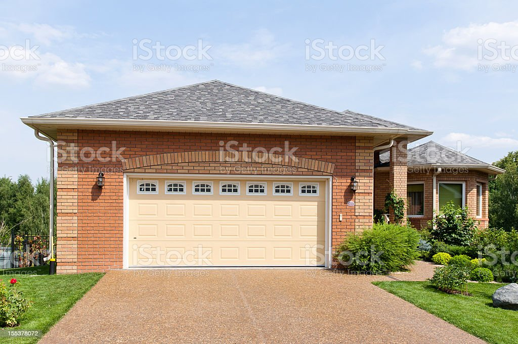 Large brick garage in a suburban environment on a sunny day stock photo