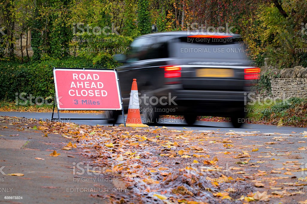 Large car speeding past a 'Road ahead Closed' sign stock photo