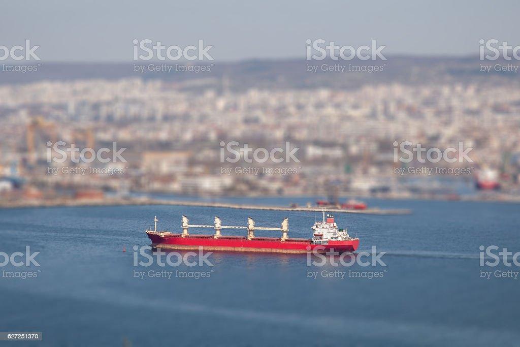 Large cargo ship arriving in port. Tilt-shift effect stock photo