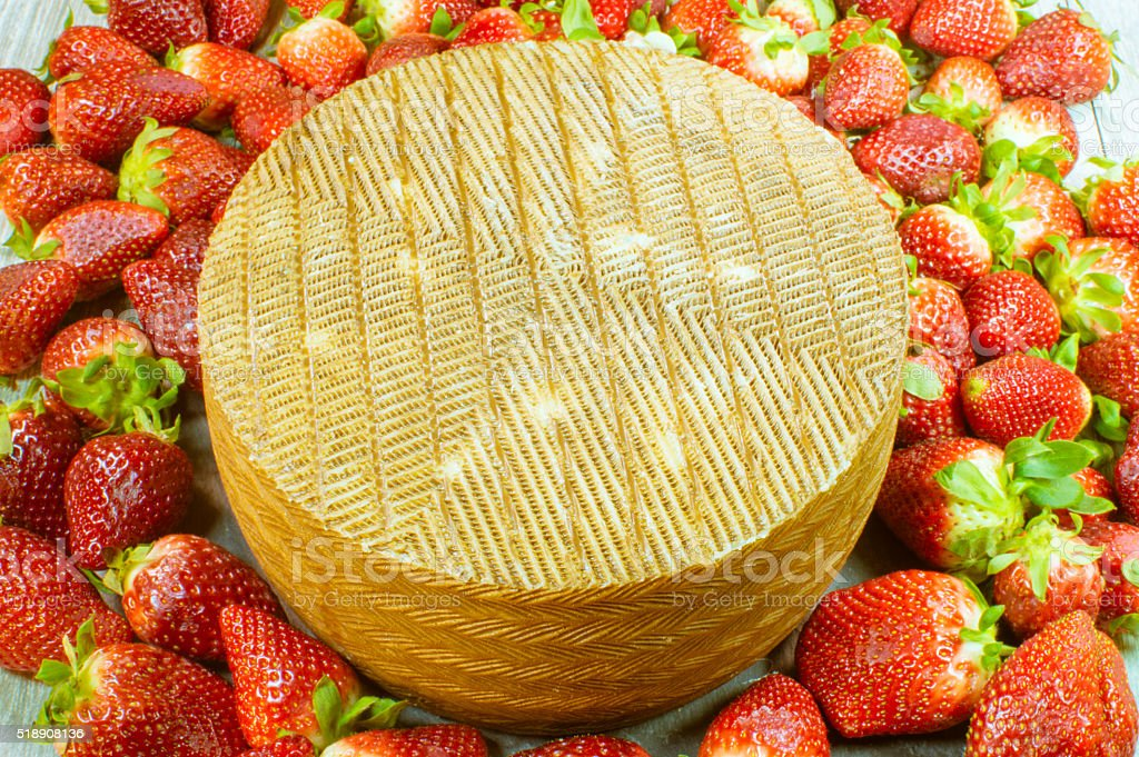 queso grande rodeado de fresas stock photo
