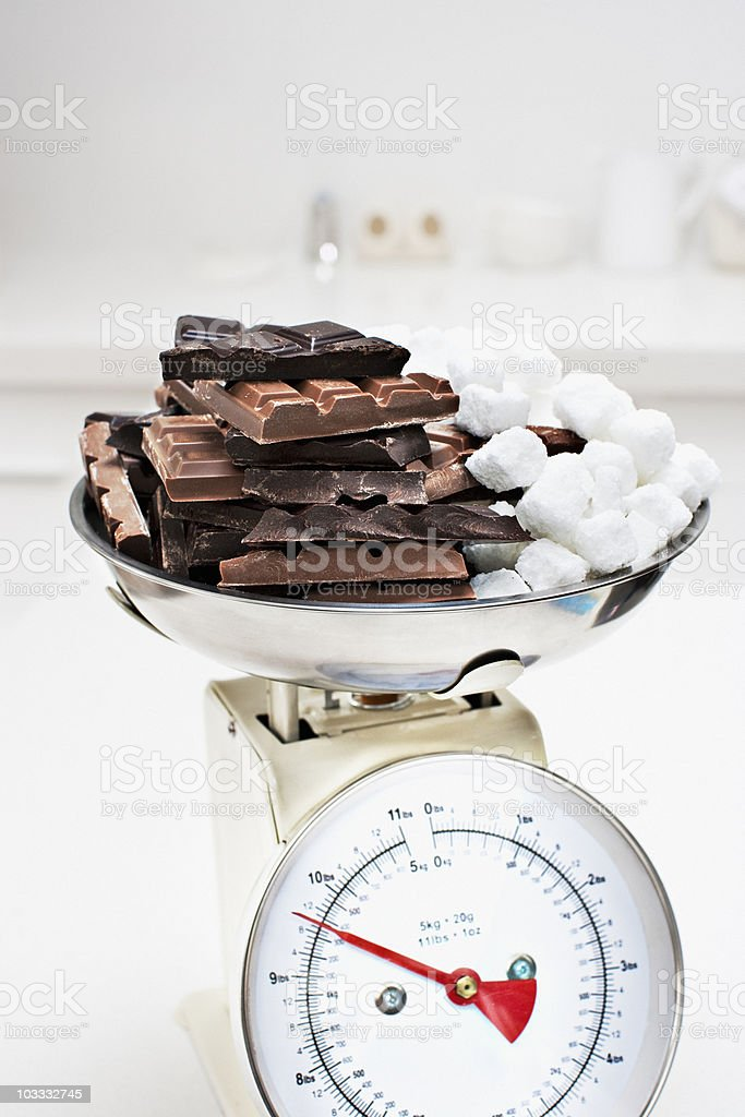 Large chocolate bars and sugar cubes on scale stock photo