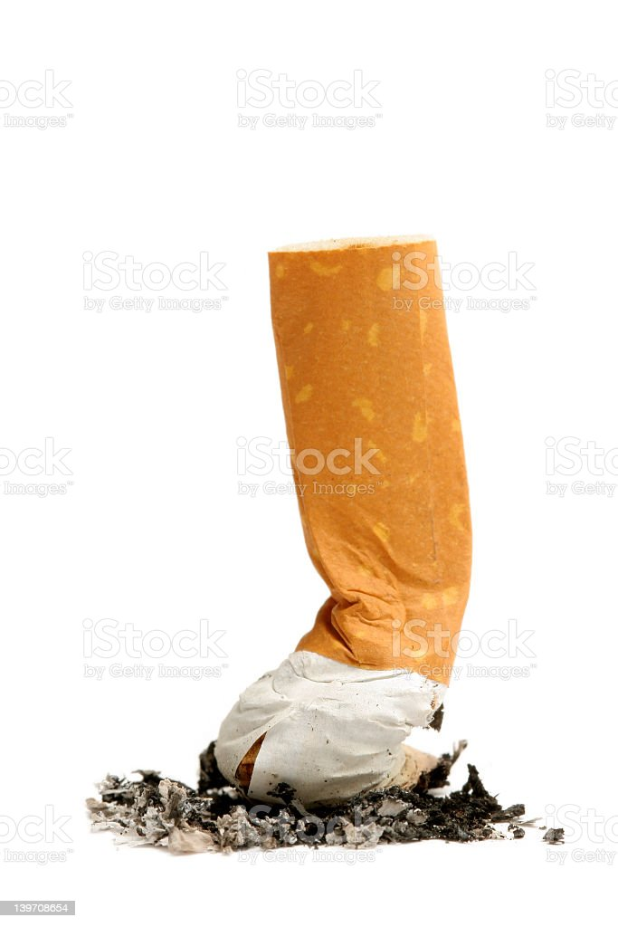 Large cigarette butt being pushed into the ground royalty-free stock photo