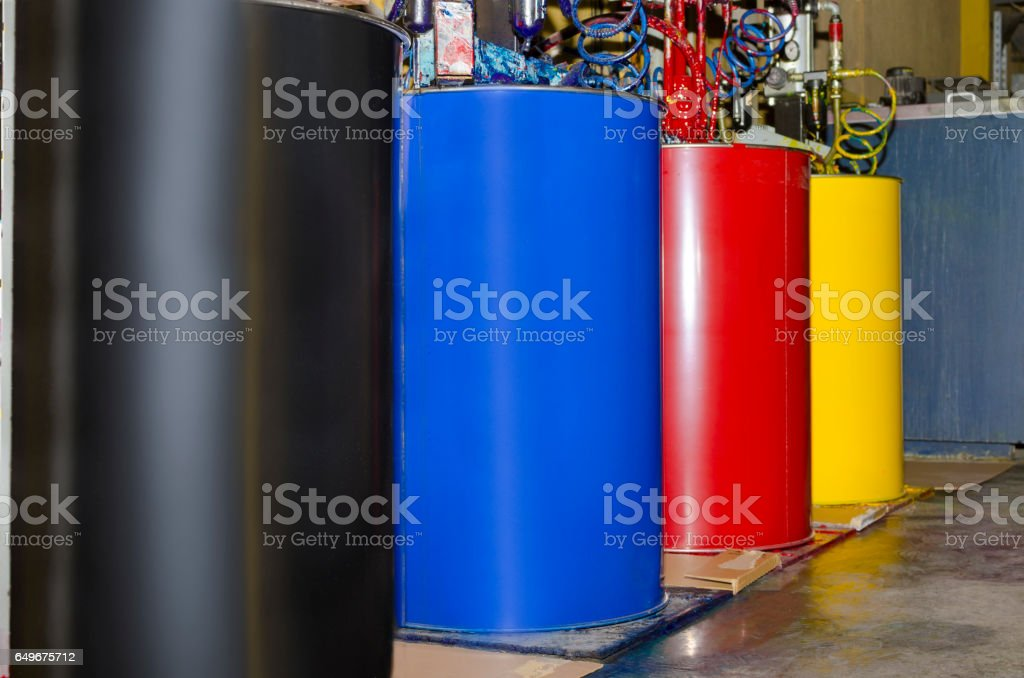 Large colorful barrels of ink in print production plant. Paint for printing roll of paper stock photo