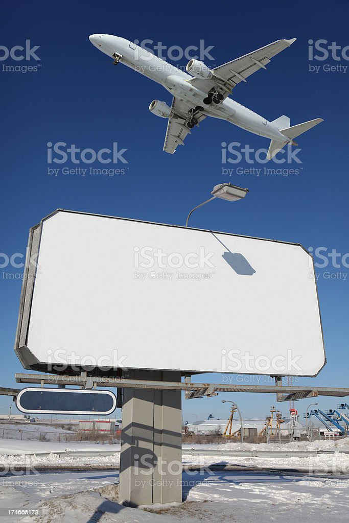 Large commercial sign with Airplane passing over royalty-free stock photo