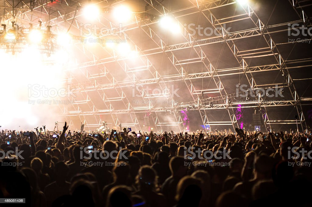 Large Concert Crowd Hands In Air With Light Effects stock photo
