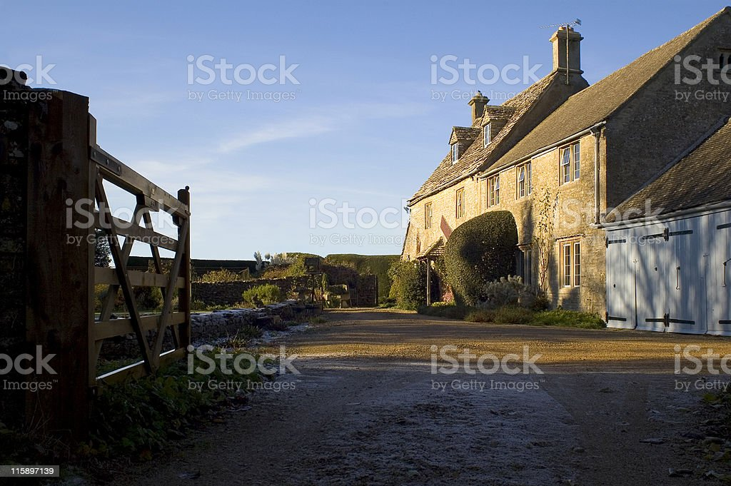 A large country cottage styled house with farm yard gates royalty-free stock photo
