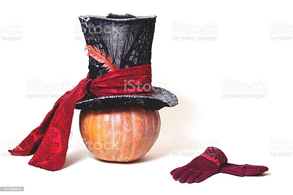 Large cylindrical hat on orange pumpkin. Near gloves stock photo