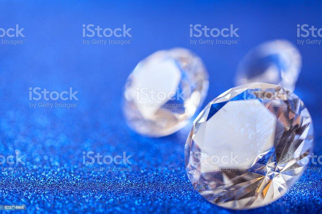 Large diamonds laid on blue sparkling background, macro. Brilliant closeup stock photo