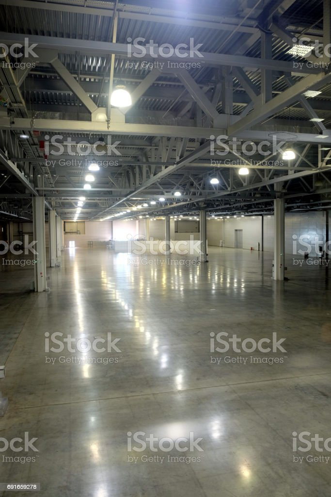 Large empty warehouse inside in industrial building with a high ceiling and artificial lighting stock photo