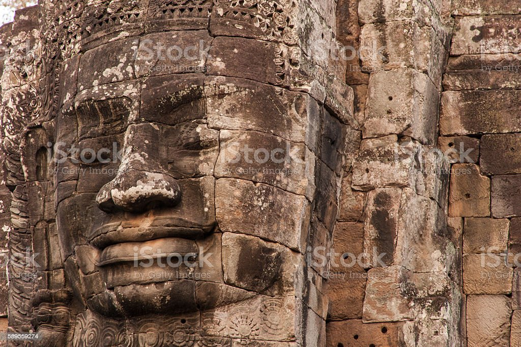 Large faces on ancient stone temples Cambodia. stock photo