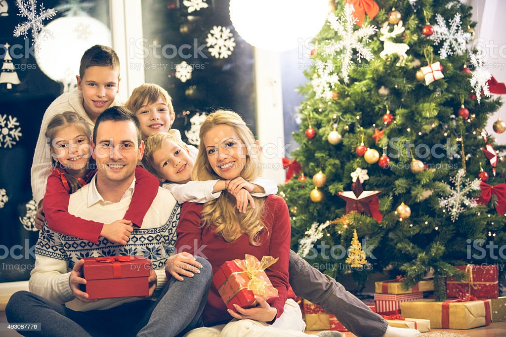 Large family of six by the Christmas tree stock photo