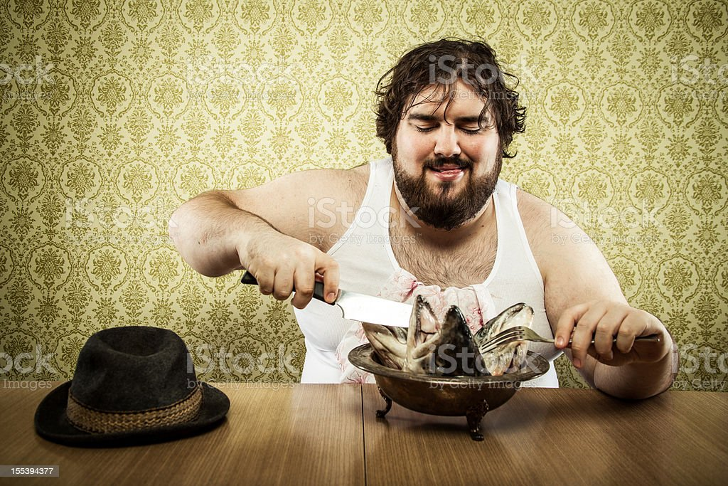 Large fat man eating fish head soup at wood table stock photo