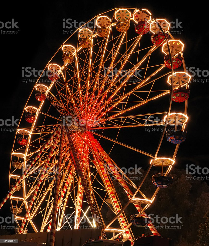 Large ferris wheel illuminated with orange light at night royalty-free stock photo