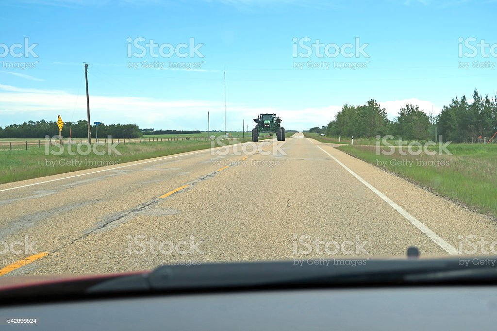 Large field sprayer coming down country road- car view stock photo