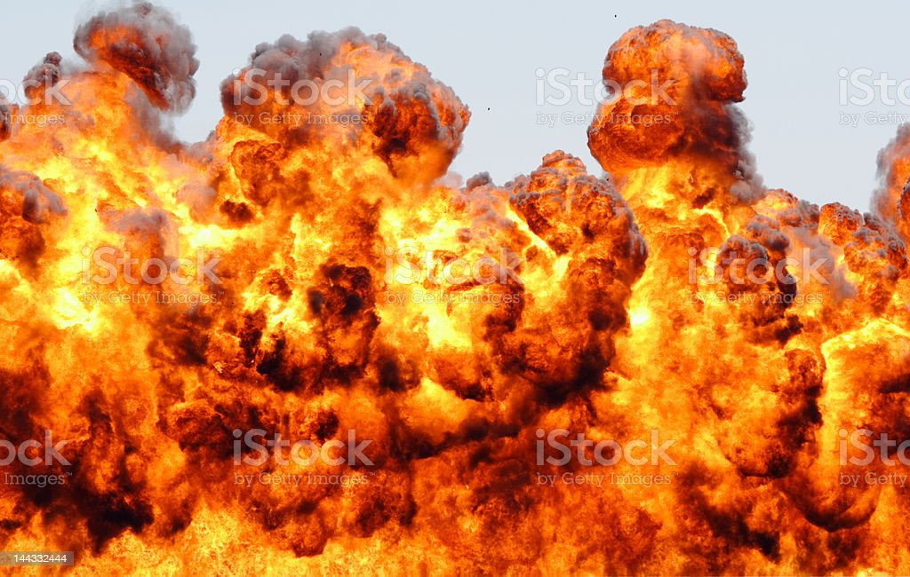Large fiery explosion throwing flames skyward stock photo