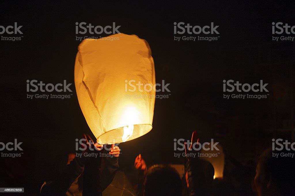 A large, floating paper lantern sent up into the sky stock photo