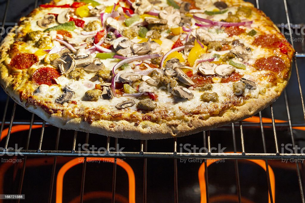Large fresh pizza baking in oven stock photo