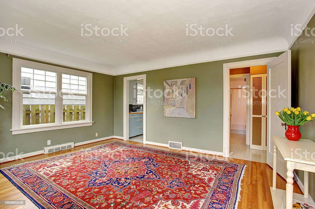 Large front room with chic decor, red rug, and green walls.