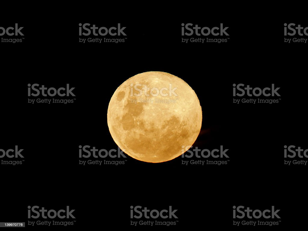 Large, full, yellow moon against a dark sky royalty-free stock photo