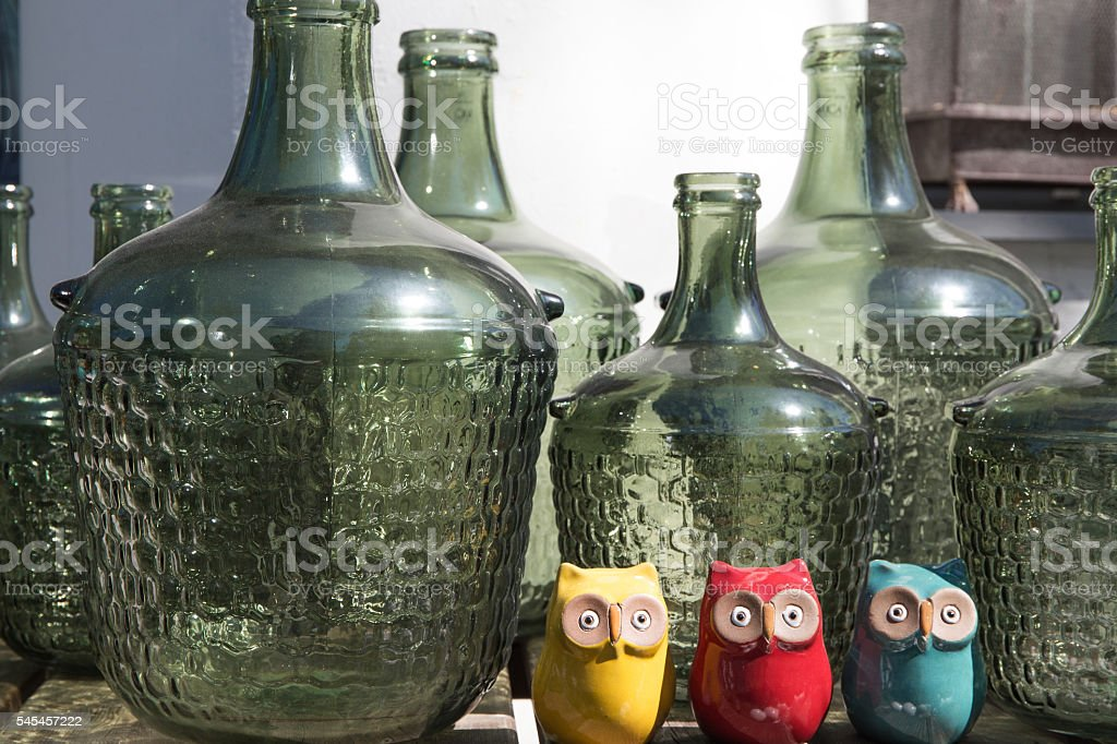 large glass bottles and three ceramic owls stock photo