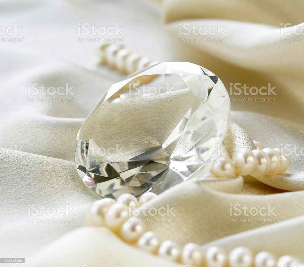 large glass diamond and pearl necklace on a soft silk stock photo