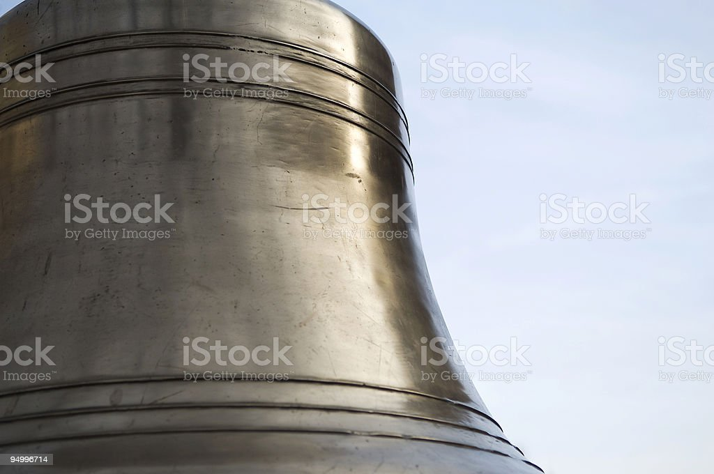 Large Golden Bell with Blue Sky in background stock photo