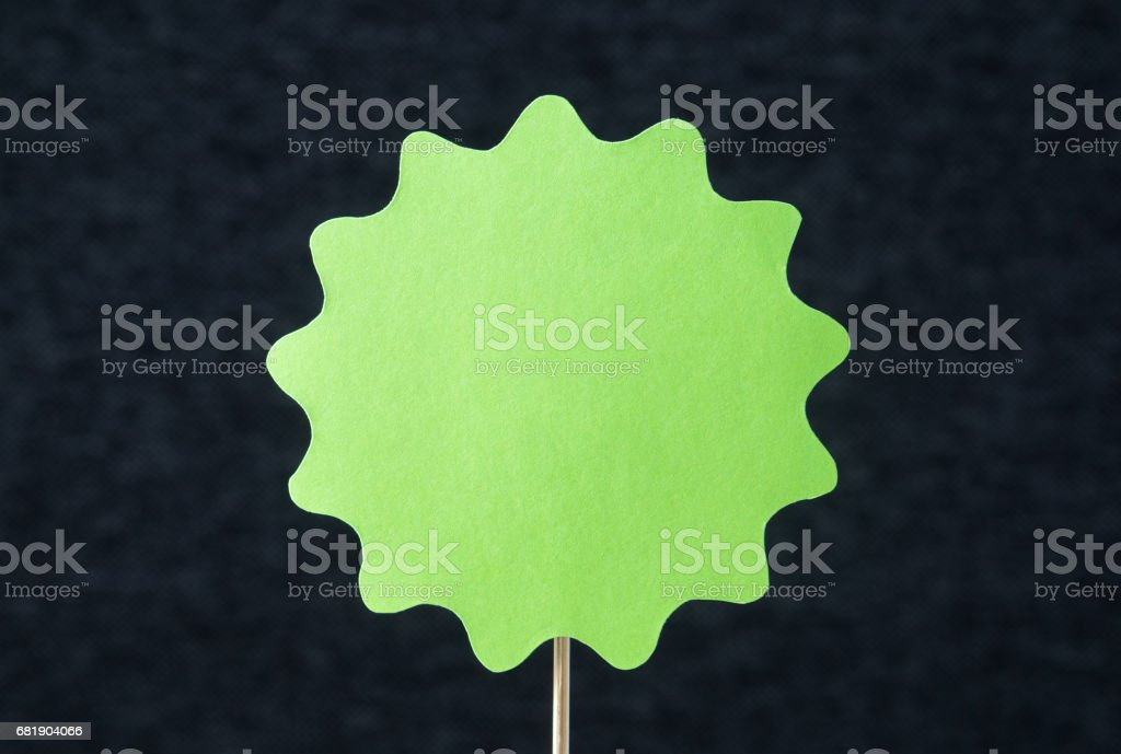 Large green shaped circle cut from cardboard on a wooden stick. Template for round paper badge, label, sign, plague, banner or design element with dark gray background and empty blank copy space. stock photo