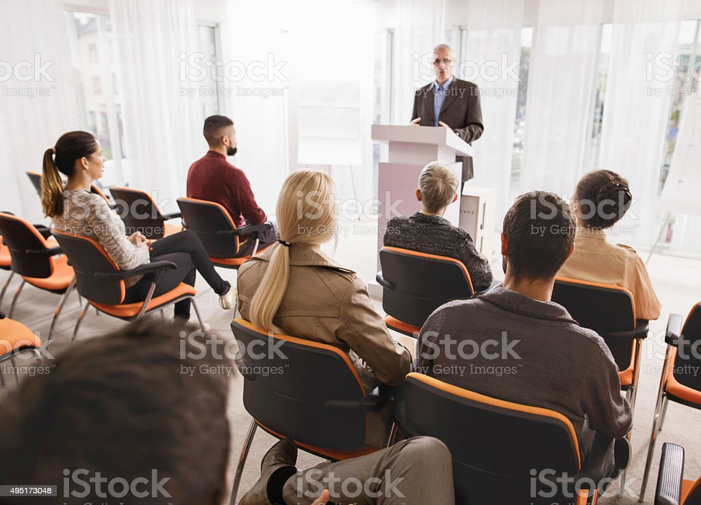 Large group of business people attending a seminar. stock photo
