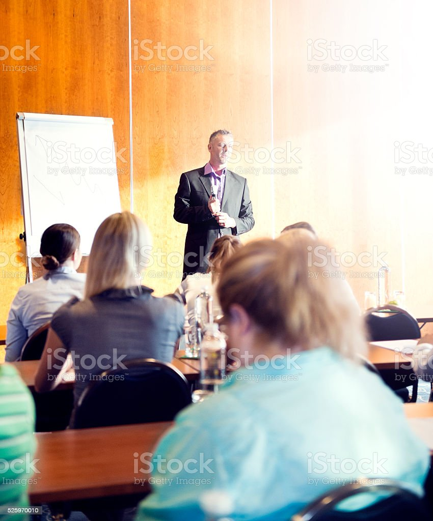 Large group of business people attending a seminar stock photo